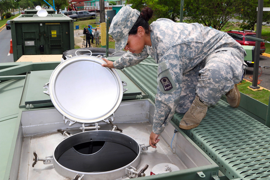 Photograph of a National Guard member checking a portable water tank