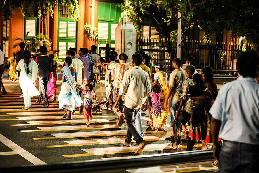 Photograph of Chennai residents in a well-lit crosswalk at night
