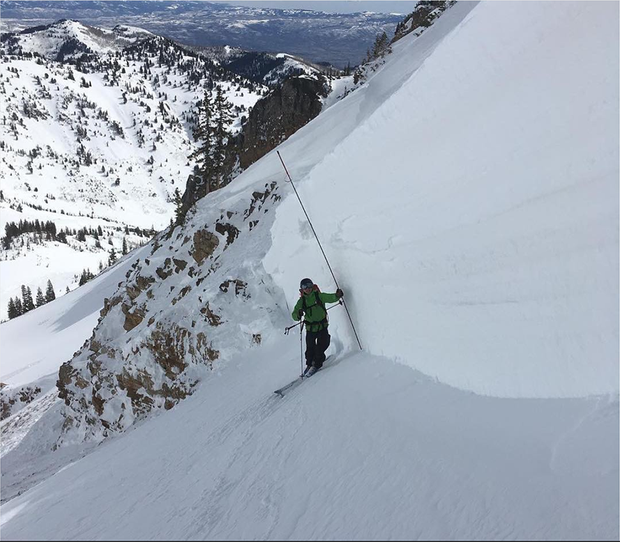 Man measuring side of snow bank in the mountains.