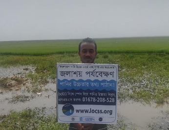 Man holding sign written in Bangla explaining the Citizen Science lake project.