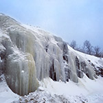 Photo showing frozen water cascading over rocks.