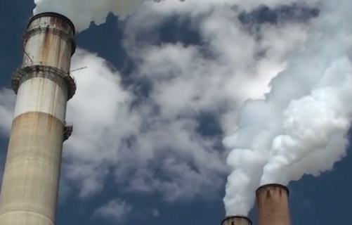 Photo of industrial smoke stacks.