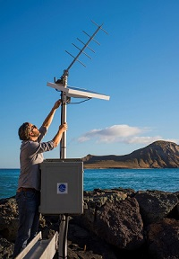 Image of Dr. Philip Thompson adjusting a solar panel on a tide gauge.