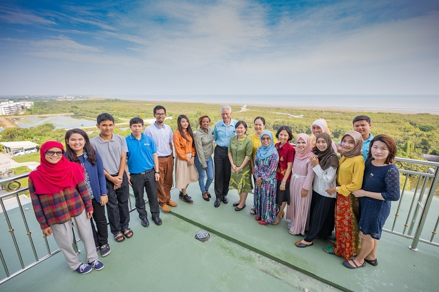 Image of Dr. McNeil standing with his students on a balconey overlooking the Gulf of Thailand.