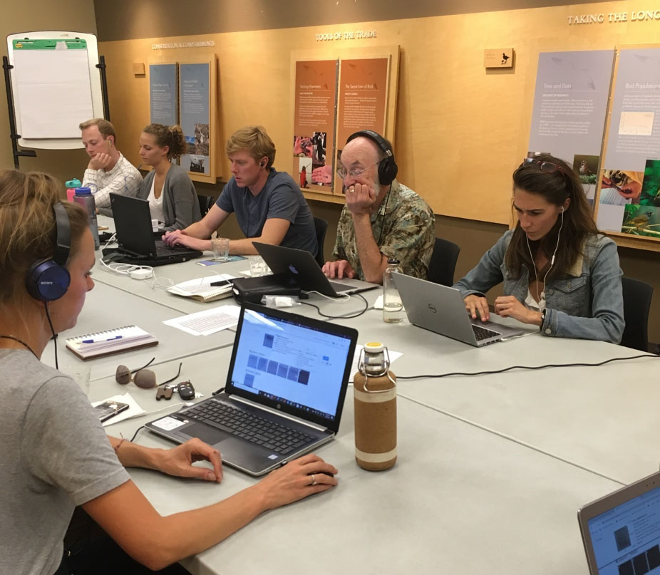 Photo of citizen scientists at laptops gathered to work on a