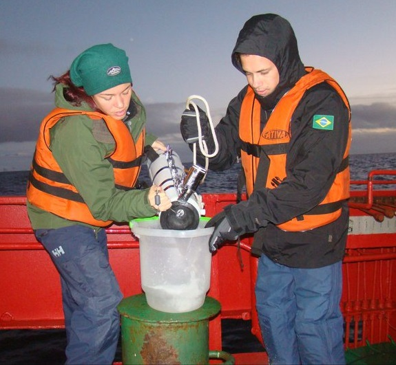 Image of Dr. Lange and a colleague standanding aboard a ship in the open ocean and wearing life vests and other protective gear. Both scientists are dumping water from a collection bottle into a sampling container. Dr. Araujo wears a Brazilian flag patch on his jacket and stands on Dr. Lange's left side.
