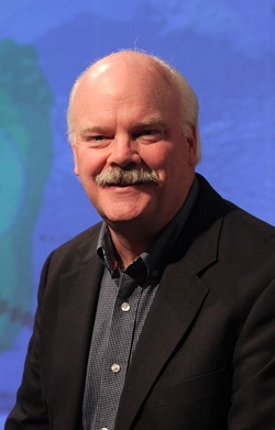Headshot of Dave Jones wearing a sport coat and sitting in front of a weather map.