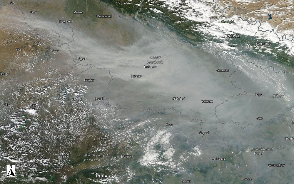 NASA Worldview image of India showing a milky-white cloud of aerosols from agricultural burning extending from the southeast to the northwest; bright white clouds are seen to the south and north of the milky white aerosols. Indian city names are overlain on the image, with New Delhi near the center.
