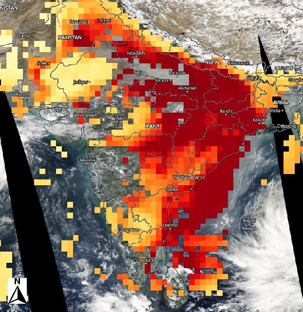 NASA worldview image of India showing extremely high aerosol concentrations indicated in red roughly tracing the outline of the milky white layer in the previous image.