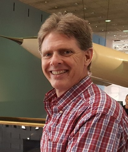 Headshot of Dr. Kurt Thome wearing a red plaid Oxford shirt and standing in front of a rocket suspended from the ceiling of the National Air and Space Museum.