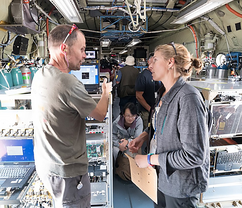 Image of Dr. Fischer talking with her colleague Dr. Frank Flocke inside a C-130 research aircraft. The aircraft interior is bare steel with instruments throughout the cabin. Fluorescent lights hang from the ceiling.