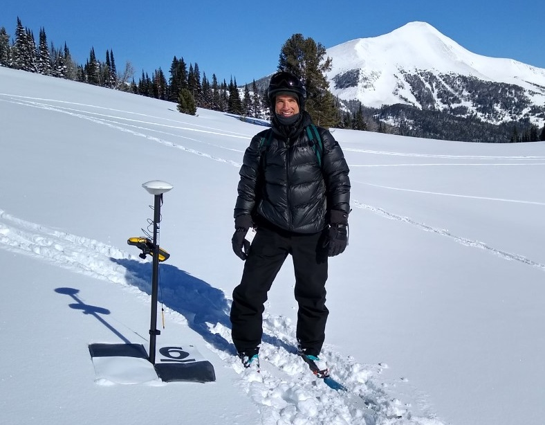 Dr. Sproles wearing all black snowgear standing on fresh white snow next to a GPS receiver. A mountain in the background has fresh snow on top, grading to bare black earth farther down the slope.