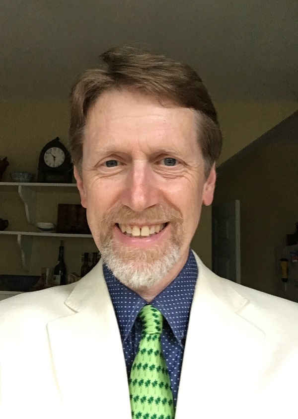 Indoor headshot of Dr. Chris Lynnes wearing a white suit with a green necktie.