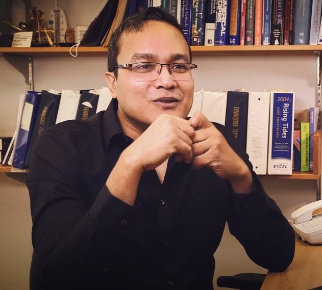 Image of Dr. Hossain sitting at his desk wearing a black shirt; rows of books line the walls behind him.