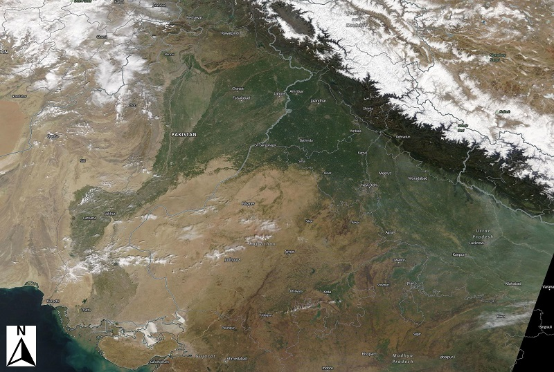 Satellite image of Asia showing the snow-capped Himalayas in the upper right with a greenish strip running from northeast to southwest indicating the path of the Indus River through Pakistan and into the Arabian Sea.