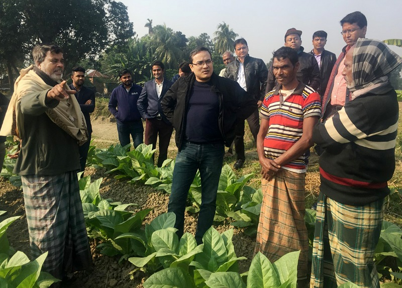 Image of Dr. Hossain standing in a planted field and wearing black talking with several farmers wearing native dress.