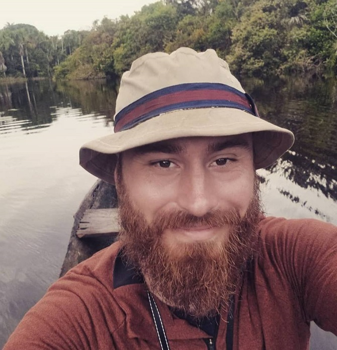 Selfie of Dr. Bullock sitting in a canoe in the middle of a river with the Amazon rainforest in the background.