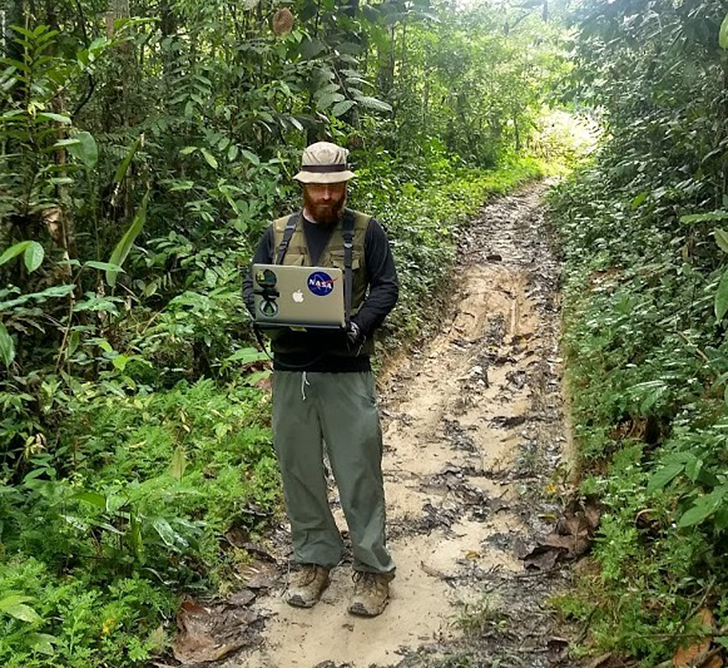 Dr. Bullock standing on a muddy road surrounded by dark green vegetation. He wears a rainhat and a rain jacket, and is holding a laptop computer.