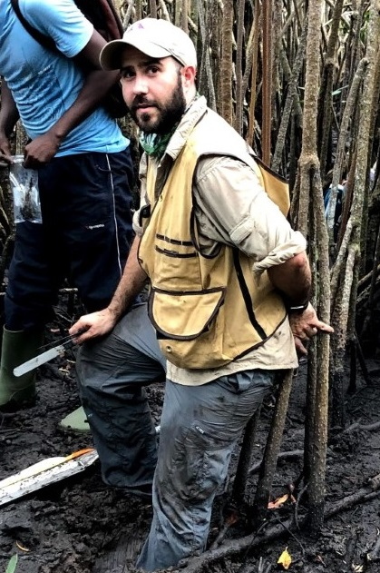Image of Dr. David Lagomasino standing in the mud in a mangrove forest. He holds a measuring tool and is wearing a vest and had. Mangrove branches surround him.