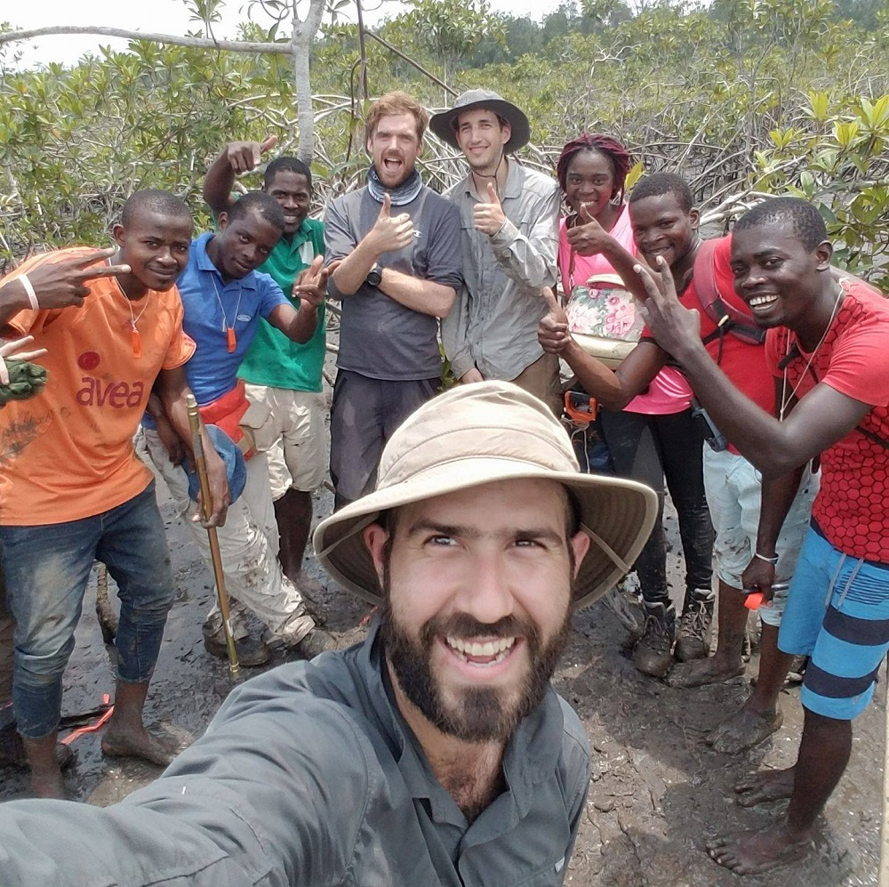 Image of Dr. Lagomasino wearing a bush hat with numerous students standing behind him in an African village.