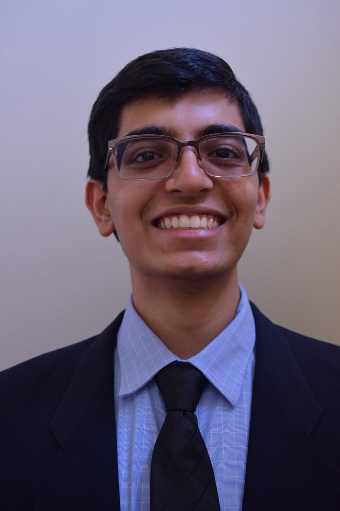 Headshot of Abhinav wearing a suit and tie.