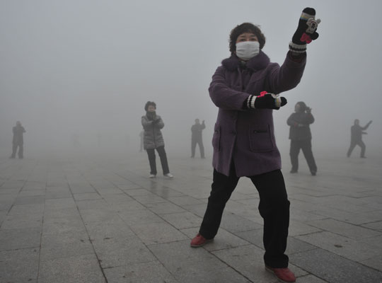Photograph of retirees performing tai chi during a smoggy day in China