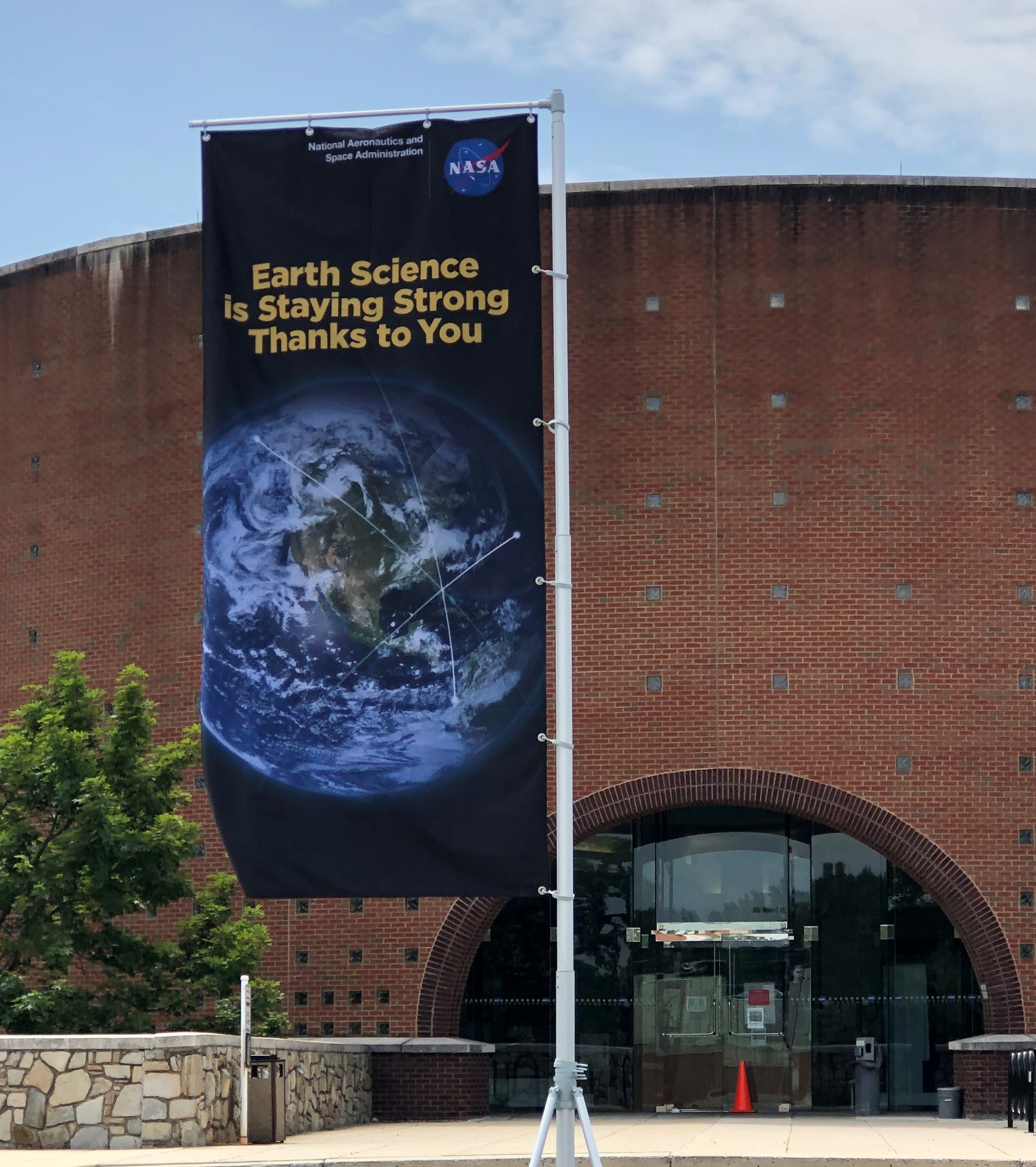 "Image of flag outside Goddard Building 32 with words ""Earth Science is Staying Strong Thanks to You"" over an image of Earth."