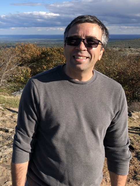 Image of Dr. Paul Siqueira standing on a mountain wearing a light sweater and sunglasses.