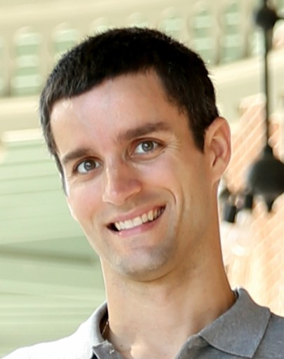 Headshot of Dr. Brian Barnes wearing an open collar shirt and standing in front of a sunny outdoor area.