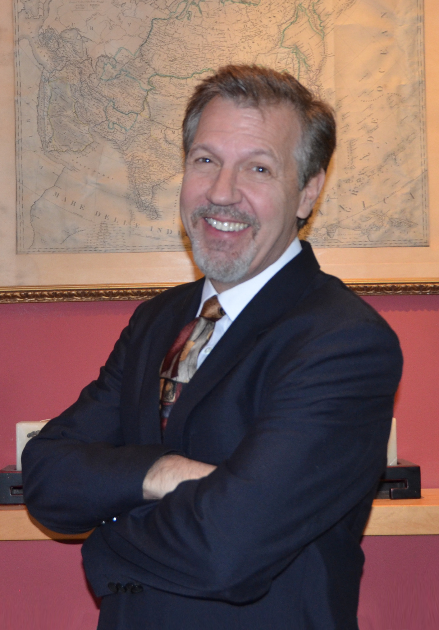 Headshot of Drew Kittel wearing a blue suit and striped necktie and standing in front of an old map of china.