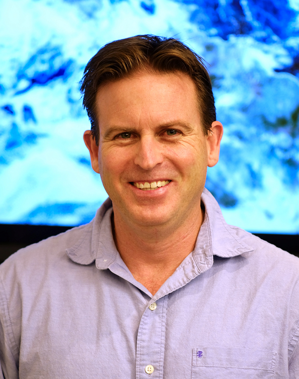 Headshot of Dr. Steven Miller wearing an open collar shirt and standing in front of a satellite image of Earth.
