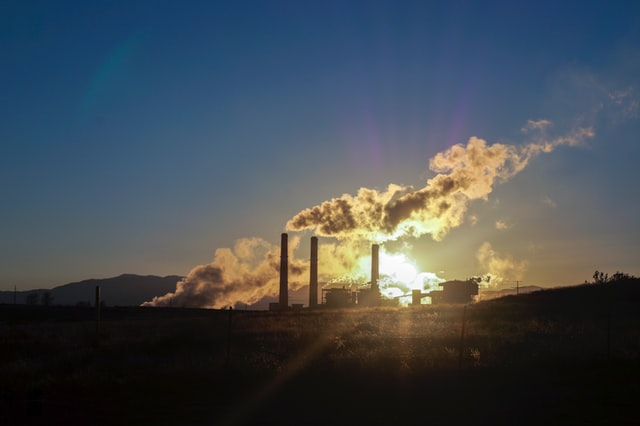 Smoke stacks at a power-generating facility. Burning fossil fuels for electricity is a source of greenhouse gas emissions.