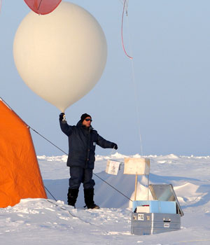 Photograph of a researcher launching an ozonesonde balloon in the Arctic