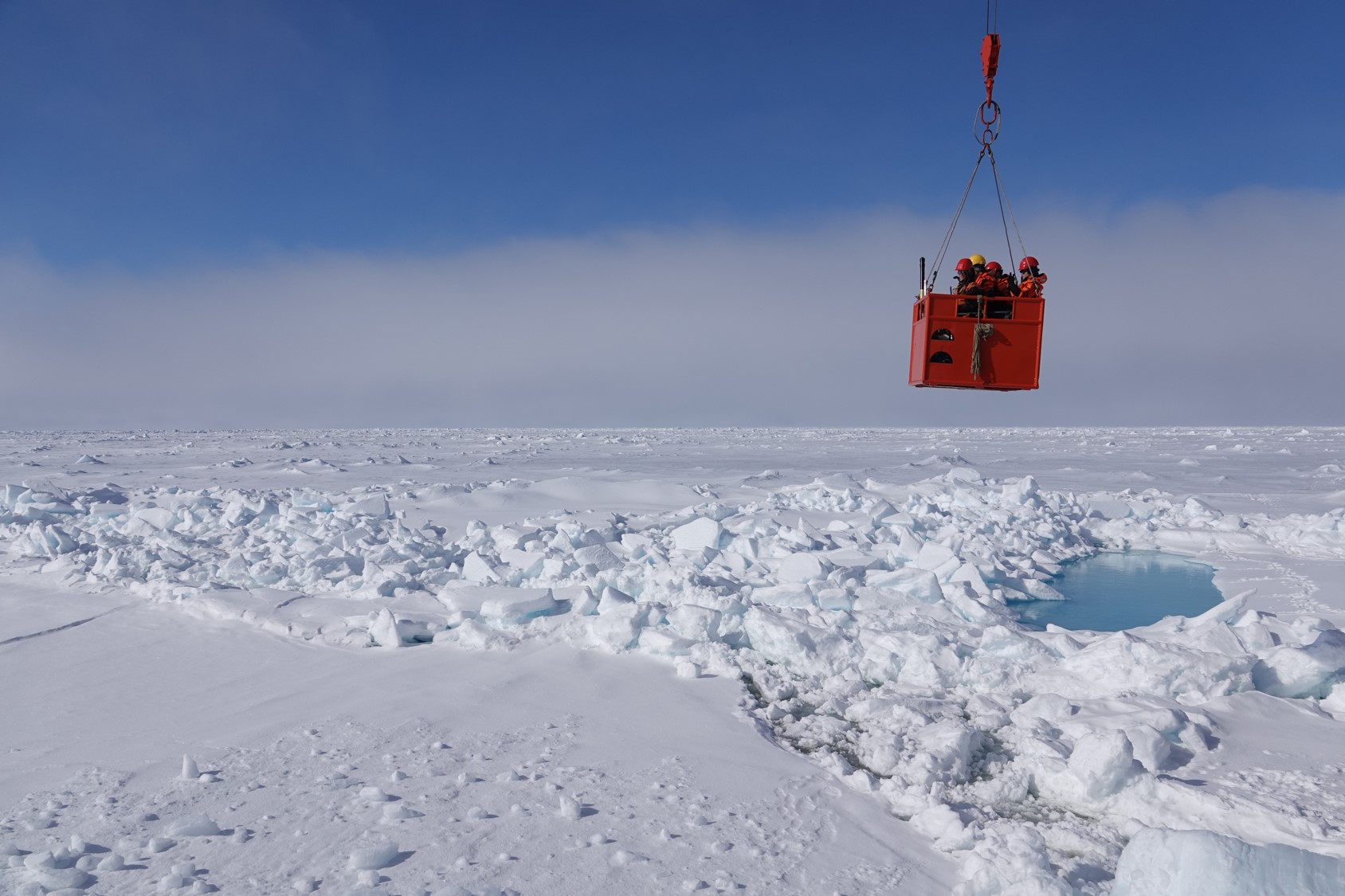A group of scientists get hoisted back their ship after taking measurements on Arctic sea ice