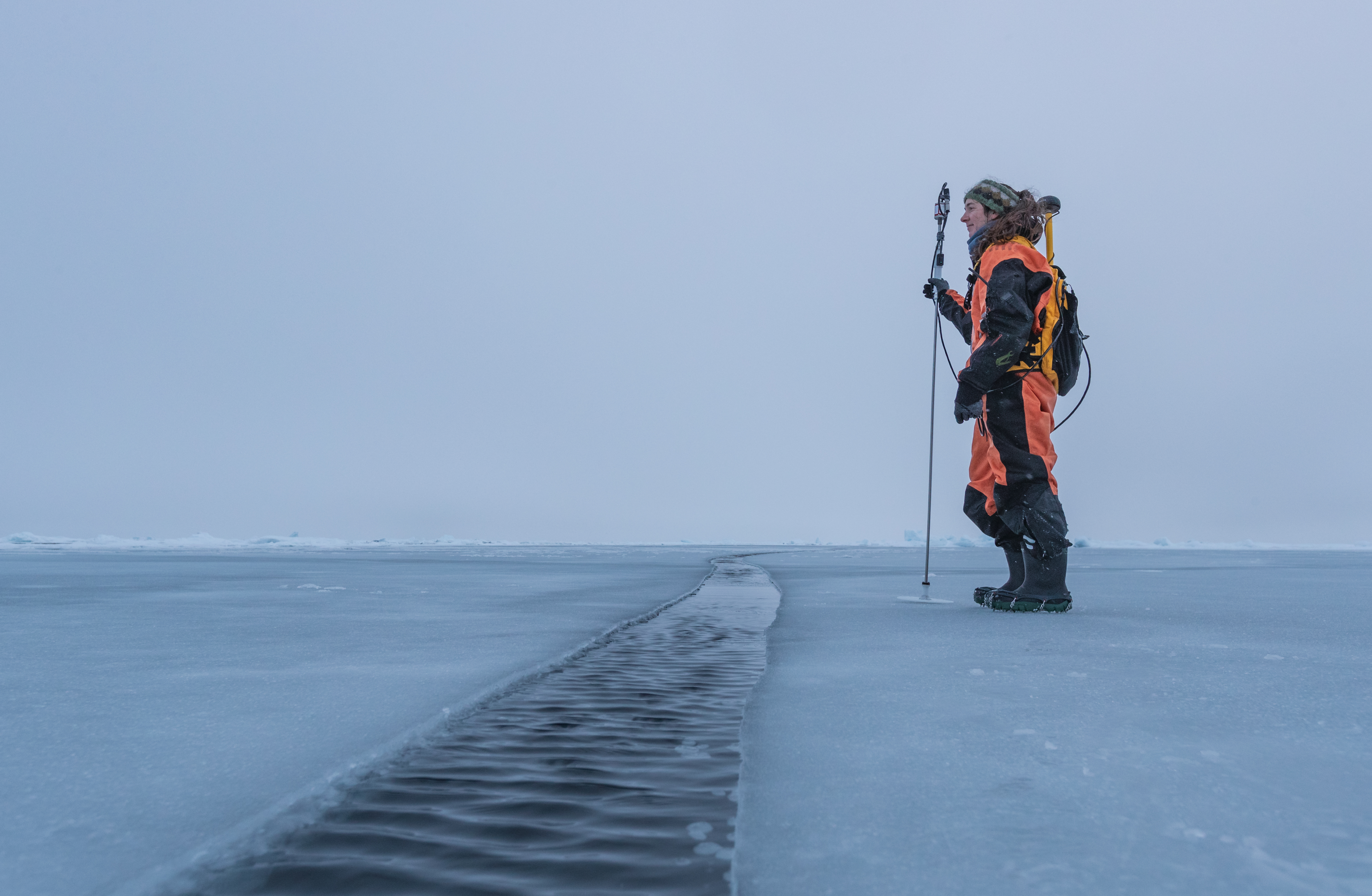 Dr. Melinda Webster stands on young sea ice in the Arctic