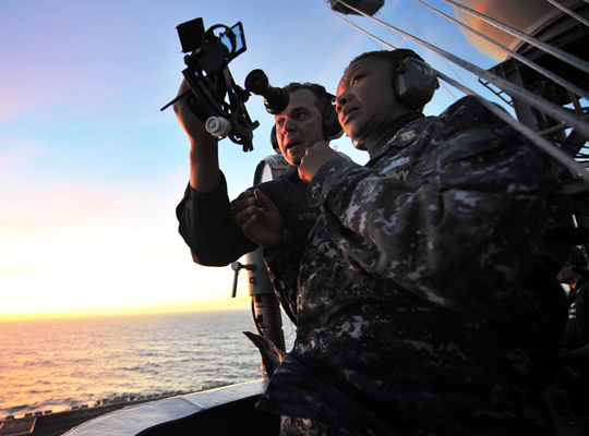 Photograph of a Navy officer training a colleague on how to use a sextant