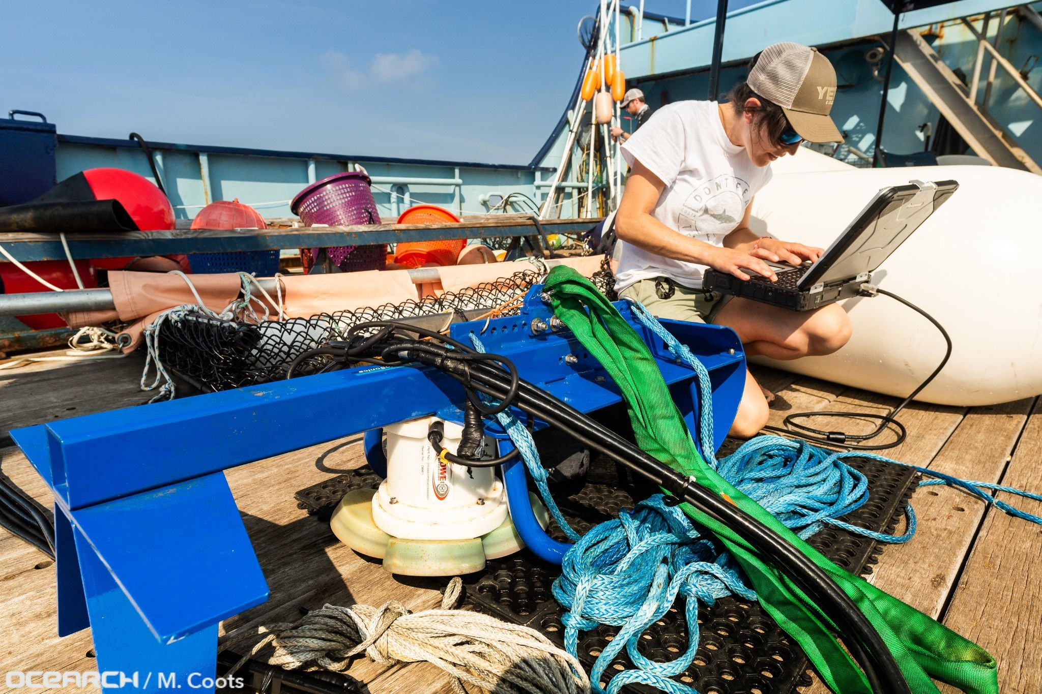 Kyla Drushka connects with the Acoustic Doppler Current Profiler before deploying it over the side of the research vessel OCEARCH.