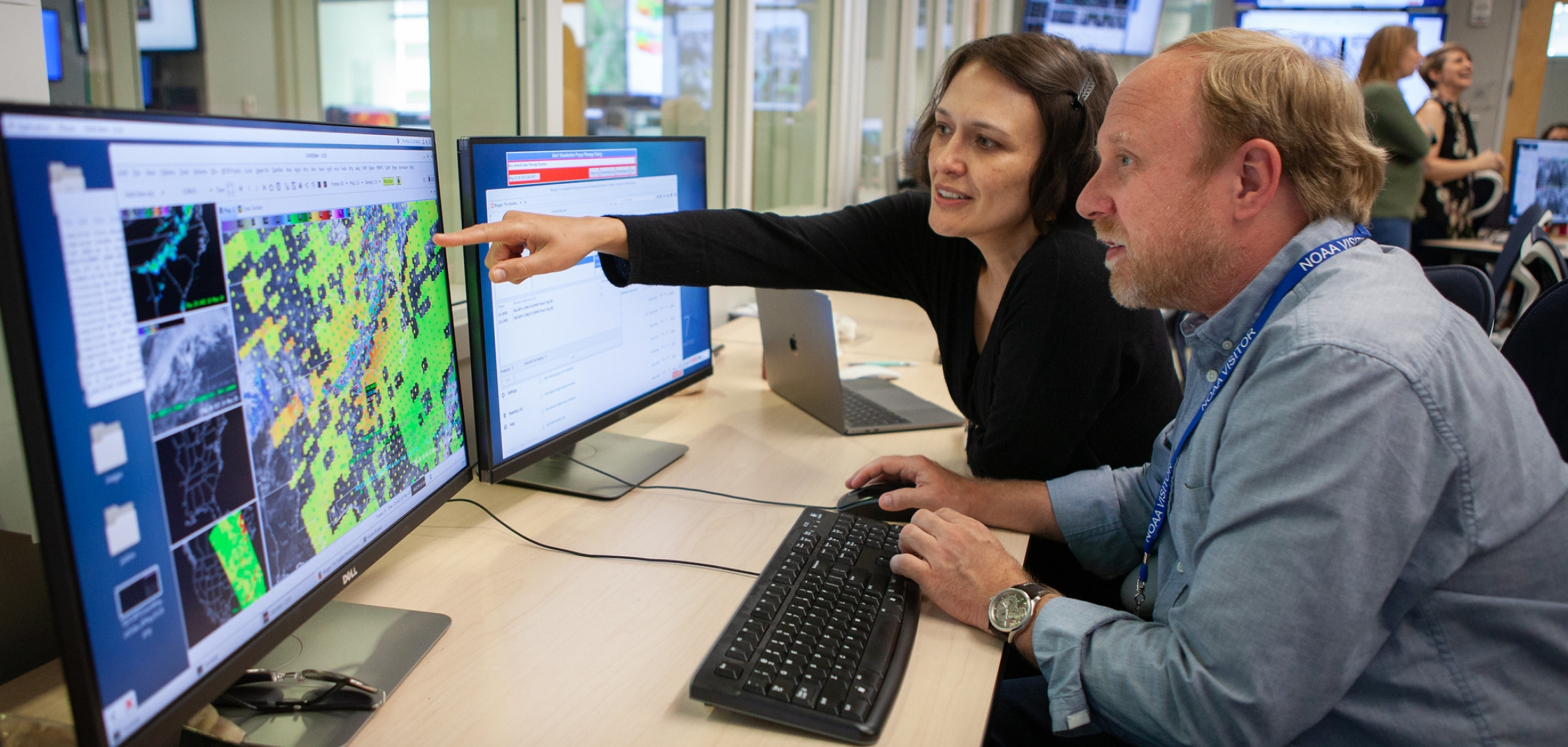 Smith and a meteorologist discuss NUCAPS at a workstation