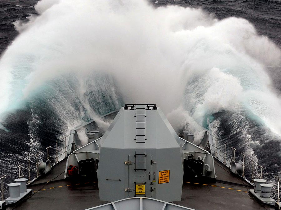 Photograph of waves crashing over a ship's bow
