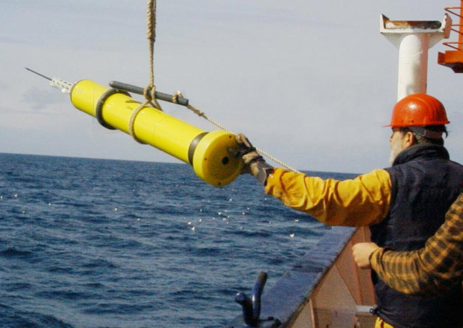 Photograph of researchers deploying a buoy from a ship