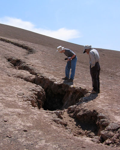 Researchers Matthew Pritchard and Gabriel Gonzalez examine a large crack caused by an earthquake in the Atacama Desert of northern Chile. A major earthquake can cause volcanic unrest hundreds of miles from its epicenter. (Courtesy M. Pritchard and R. Allmendinger)