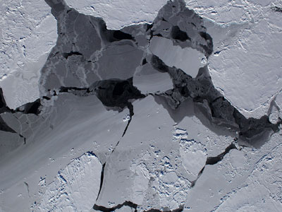 This scene shows a mixture of sea ice types commonly seen in the Southern Ocean. The different thicknesses of sea ice form a spectrum of colors and shapes ranging from dark black open water, a thin grease-like covering called grease ice, and thicker grey ice. Older sea ice has a bright white covering of snow and many chaotic deformation features visible as ridges and rubble fields caused by the continuous motion of the ice pack. (Courtesy M. Studinger/NASA)