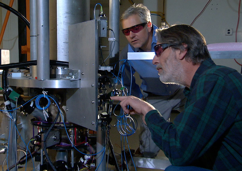 Photograph of scientists examining an atomic clock