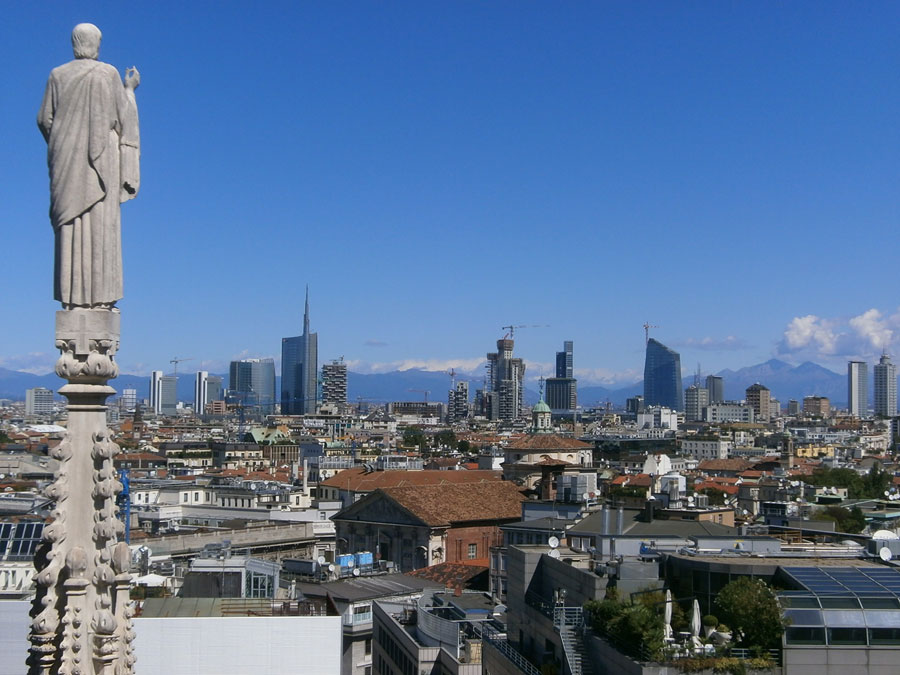Photograph of a cathedral spire against a backdrop of the Milan skyline