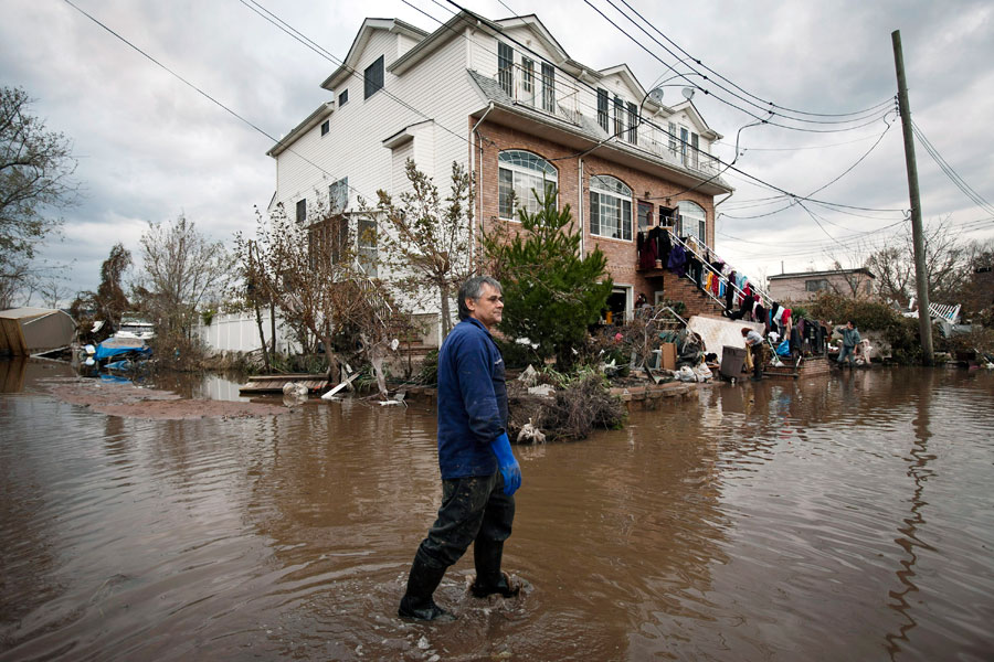 Photograph of a man wading through flooded streets in Staten Island, New York