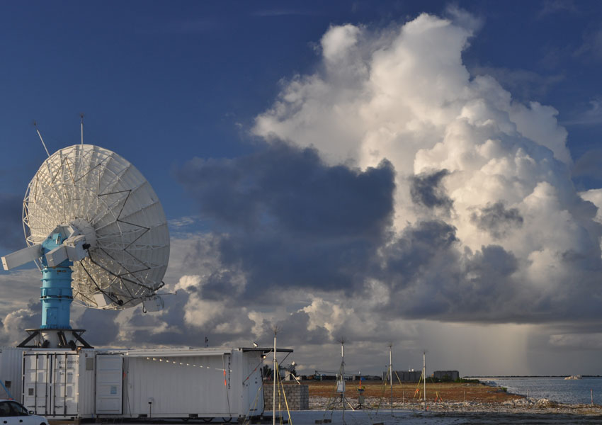 A weather radar sits on a shipping container on Addu Atoll in the Indian Ocean where the Madden-Julian Oscillation spawns. Convective clouds form in the background. (Courtesy E. Maloney/Colorado State University)