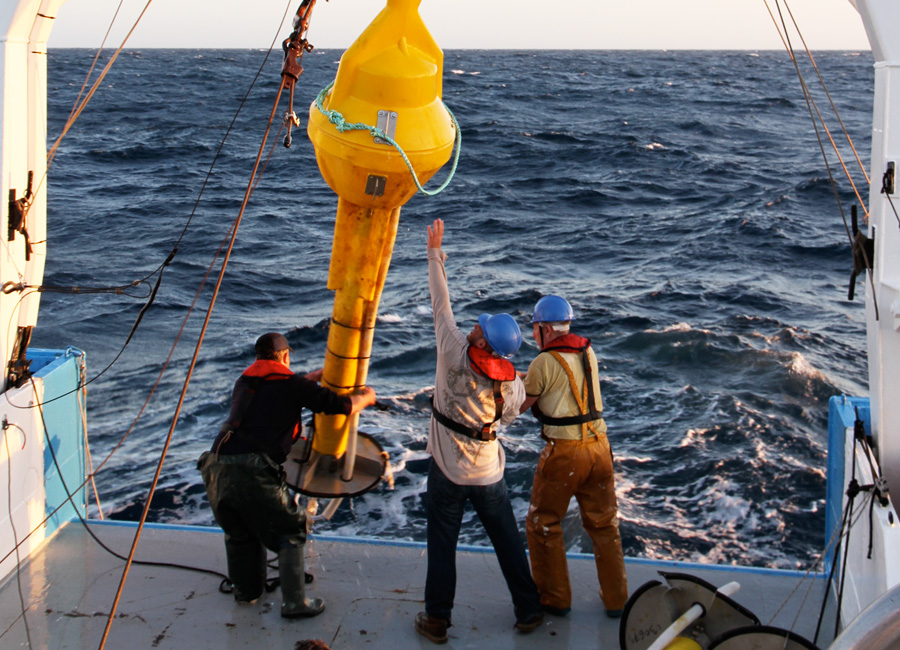 Photograph of a crew hauling an ocean buoy onboard a ship