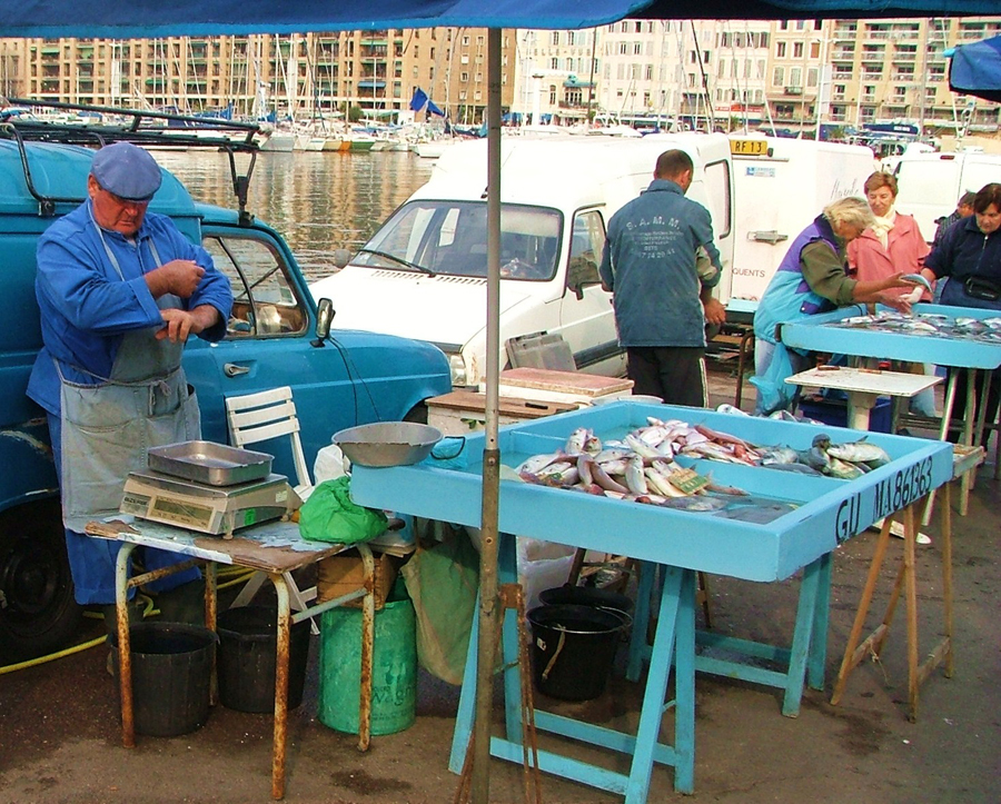 Photograph of fishmongers at a pier in France