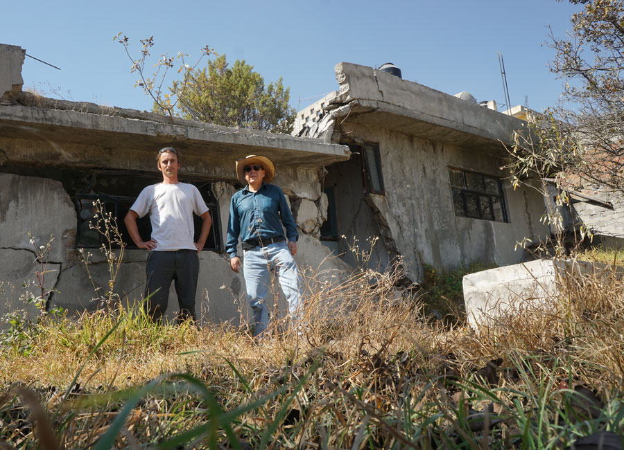 Photograph of two researchers standing in front of a fractured house