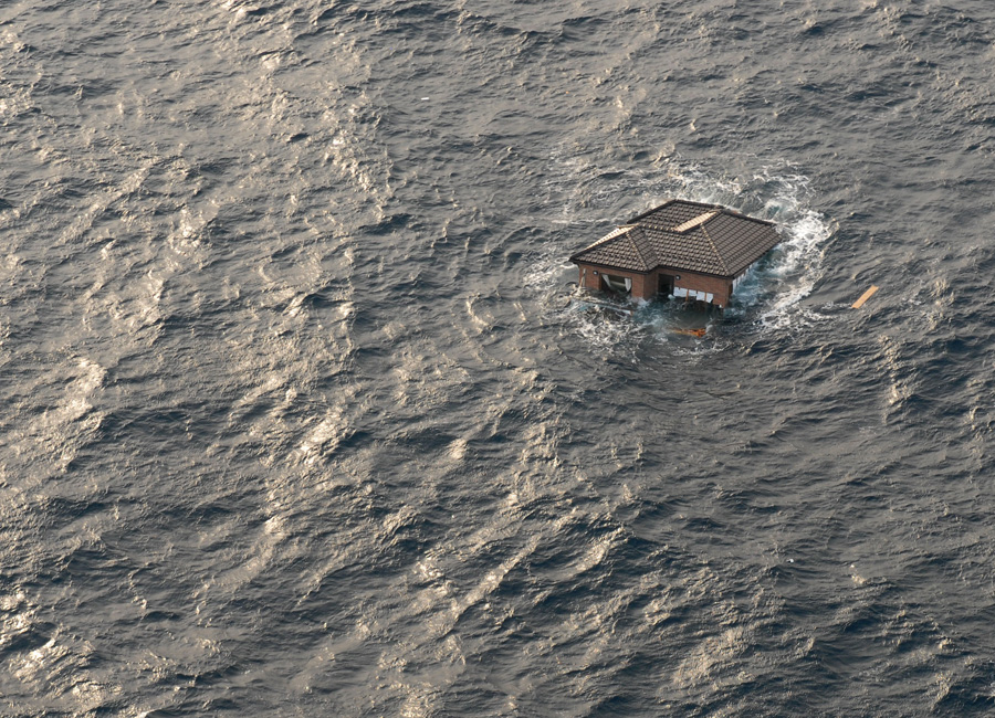 Photograph of a house drifting in the Ocean after an earthquake and tsunami in Japan